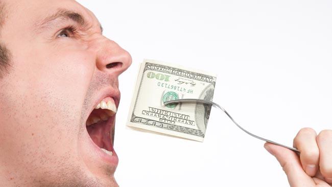 man eating hundred dollar bill close up